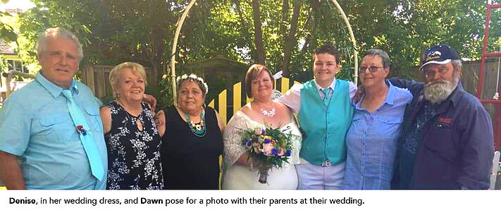 Denise, in her wedding dress, and Dawn pose for a photo with their parents at their wedding.