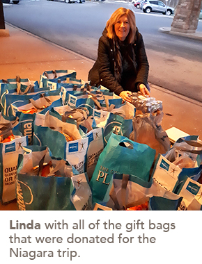 Photo of Linda with all of the gift bags that were donated for the Niagara trip.