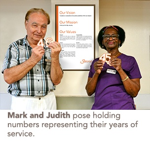 Mark and Judith pose holding numbers representing their years of service