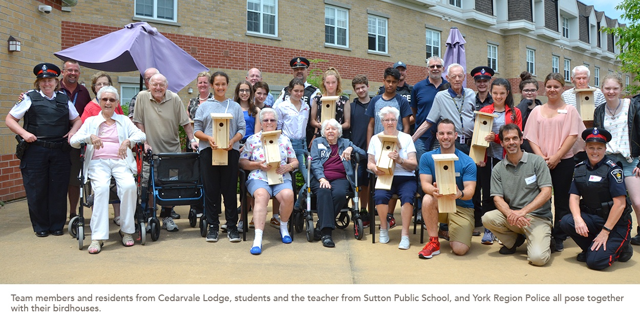 Team members and residents from Cedarvale Lodge, students and the teacher from Sutton Public School, and York Region Police all pose together with their birdhouses.