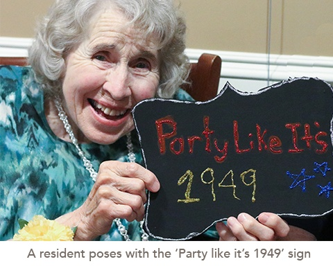 picture of a resident poses with the 'Party like it's 1949' sign