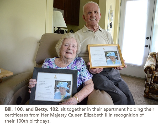 Bill, 100, and Betty, 102, sit together in their apartment holding their certificates from Her Majesty Queen Elizabeth II in recognition of their 100th birthdays.