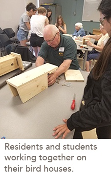 picture of residents and students working together on their bird houses