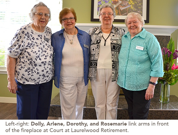 Photo of Dolly, Arlene, Dorothy, and Rosemarie link arms in front of the fireplace at Court at Laurelwood Retirement.
