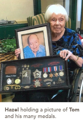 picture of Hazel holding a picture of Tom and his many medals.