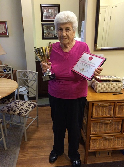 A female senior is holding a trophy and an award certificate